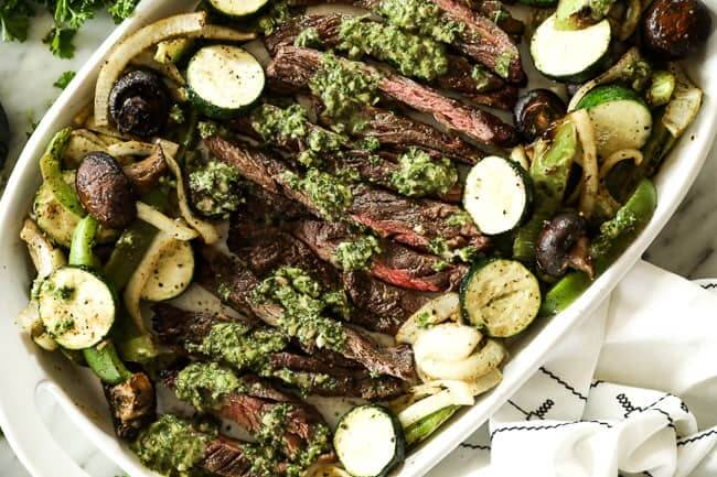 Chimichurri steak on a serving platter with grilled veggies and topped with chimichurri sauce.