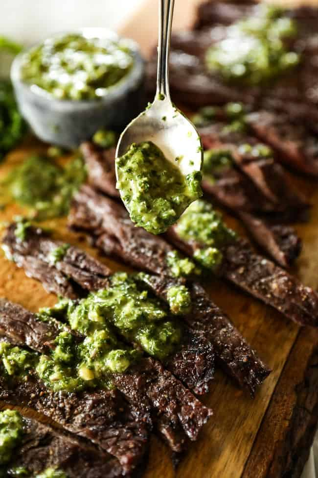 Drizzling sauce on chimichurri steak.