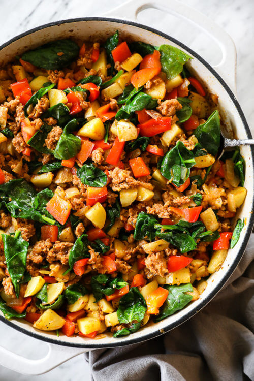 Vertical overhead image of easy chorizo hash in a skillet with a serving spoon.