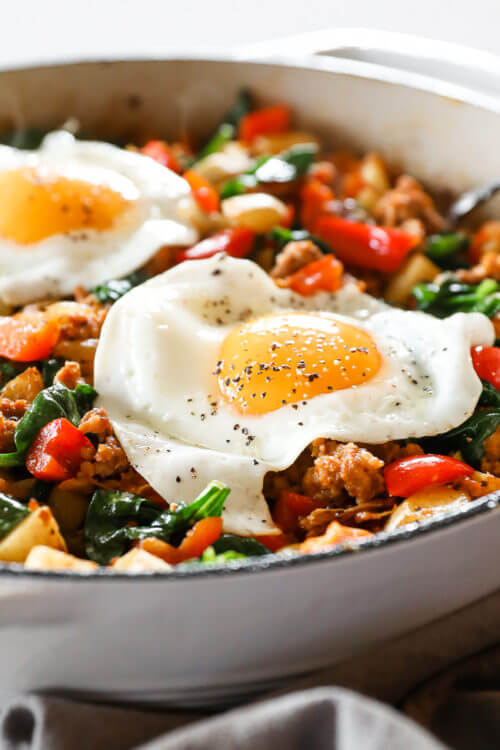 Angled vertical image of easy chorizo hash in skillet with fried eggs on top.