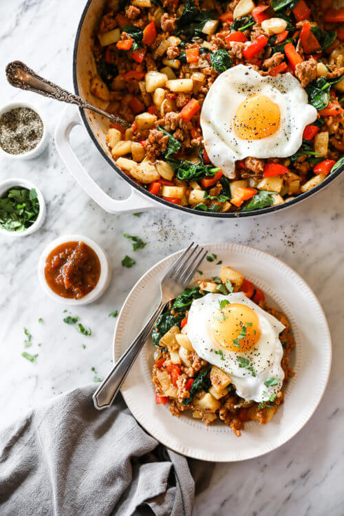 Vertical overhead image of easy chorizo hash in skillet with serving spoon and served up on a plate with a fried egg on top. Salsa, cilantro and pepper on the side.