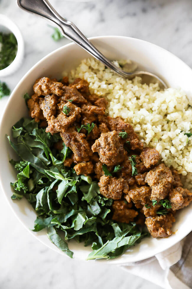 Close up image of easy curry beef in a bowl with greens and cauliflower rice.