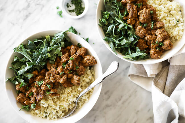 Easy curry beef bowls recipe served up in two bowls with green and cauliflower rice with forks dug into bowls. Chopped parsley on the side.