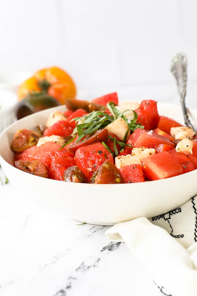 Straight on image of tomato watermelon salad in a bowl with a serving spoon. Fresh basil on top.