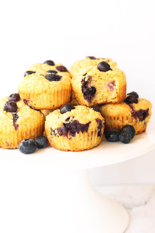 Cake stand with gluten free lemon blueberry muffins stacked on top of it. One muffin has a bite taken out of it.