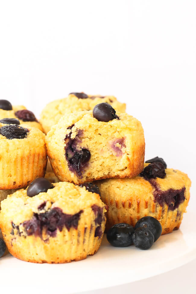 Gluten free lemon blueberry muffins on a cake stand.