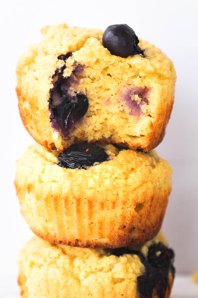 Close up image of three lemon blueberry muffins stacked. Top muffin has a bite taken out of it.