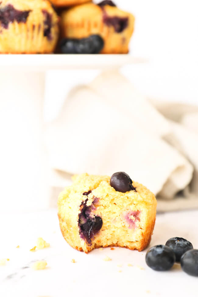 One gluten free muffin with a bite taken out of it sitting on the counter with cake stand of more muffins in the background.