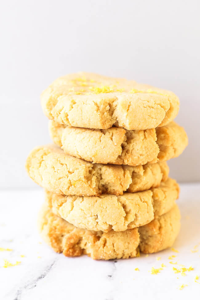 A stack of five gluten free shortbread cookies with lemon zest sprinkled on top.