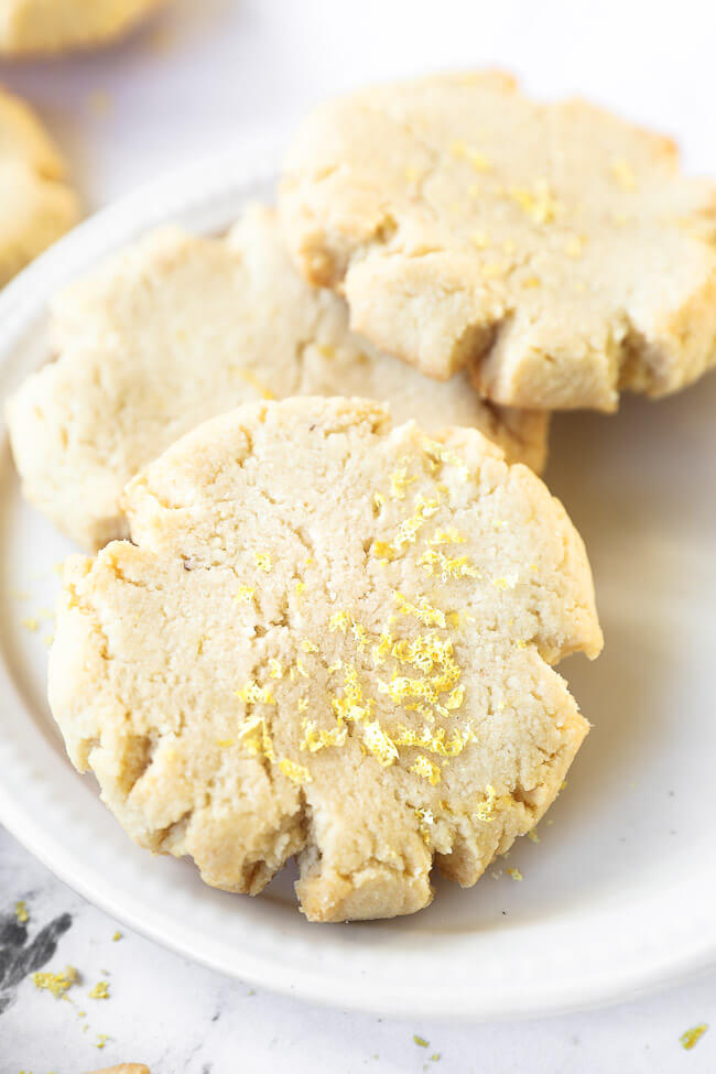 Close up angled shot of three shortbread cookies on a plate with lemon zest sprinkled on top.