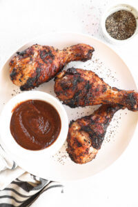 Grilled chicken drumsticks on a plate with BBQ sauce and pepper