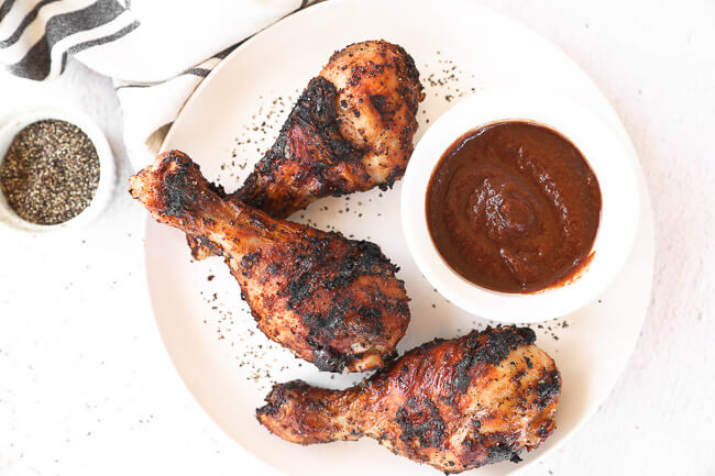 Grilled chicken drumsticks on a plate with BBQ sauce horizontal image