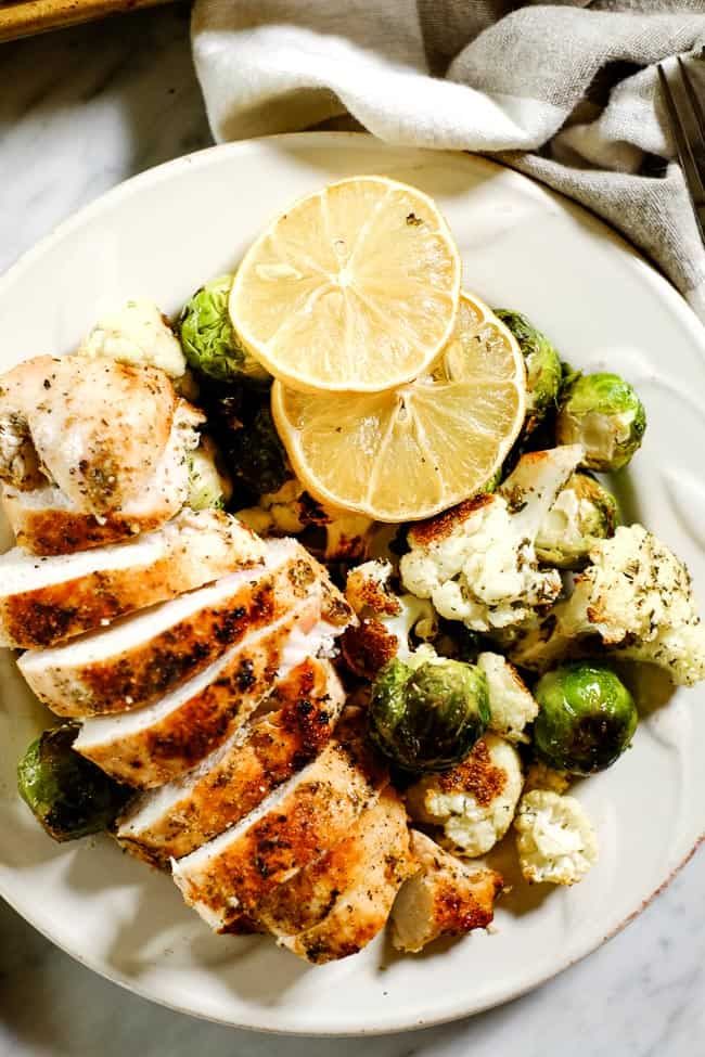 Closer up shot of easy lemon chicken served on a plate with roasted brussels and cauliflower and garnished with lemon slices.