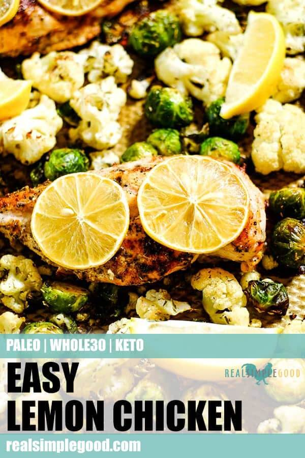 Close up of easy lemon chicken with roasted brussels and cauliflower on a sheet pan with lemon slices. Long pin for pinterest.