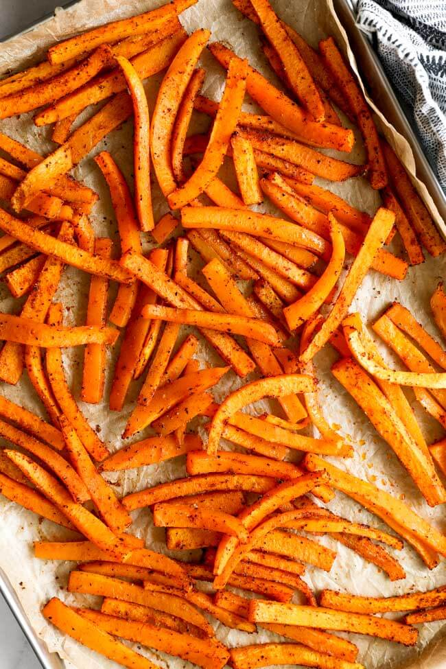 Vertical overhead image of butternut squash fries on a baking sheet.
