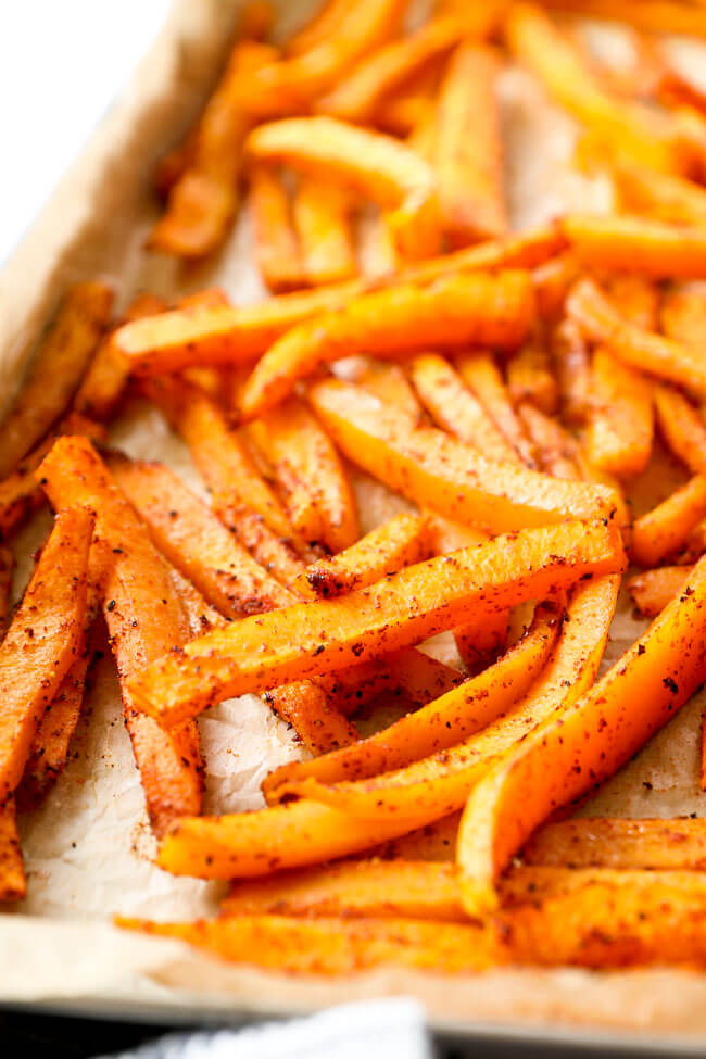 Vertical angled close up image of oven baked butternut squash fries on baking sheet.