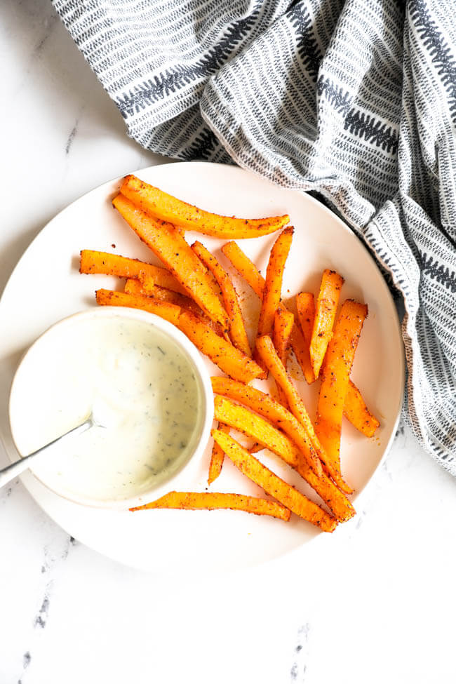 Vertical overhead image of oven baked butternut squash fries on a plate with a side of ranch dressing for dipping.