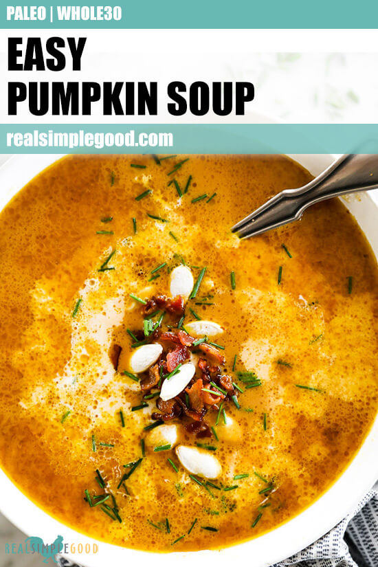 Vertical overhead close up image of pumpkin soup in a bowl with a spoon. Topped with bacon bits, pumpkin seeds and chopped chives. Text overlay at top.