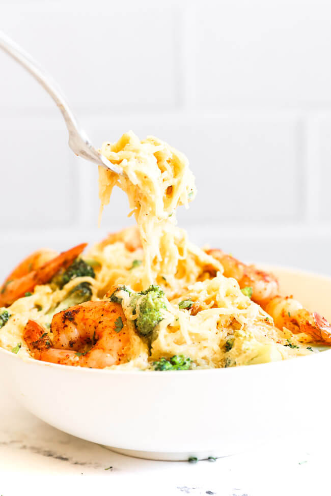 Image of scooping a forkful of spaghetti squash alfredo out of a bowl.
