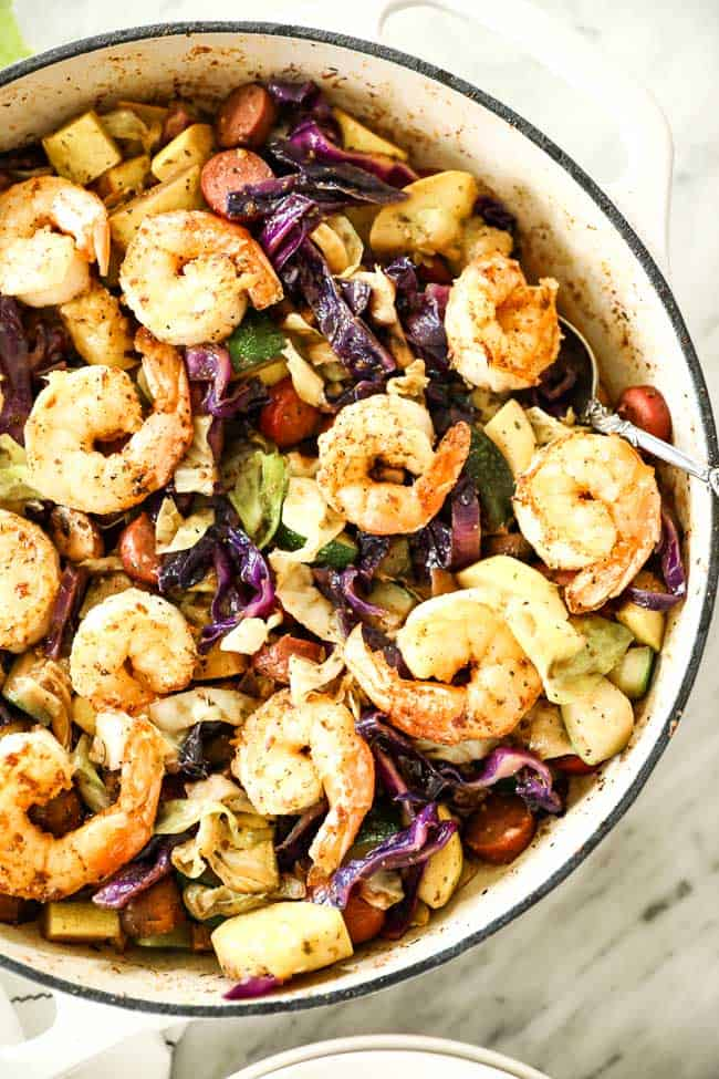 Shrimp and sausage skillet with cabbage, zucchini and mushrooms in a skillet with a serving spoon.