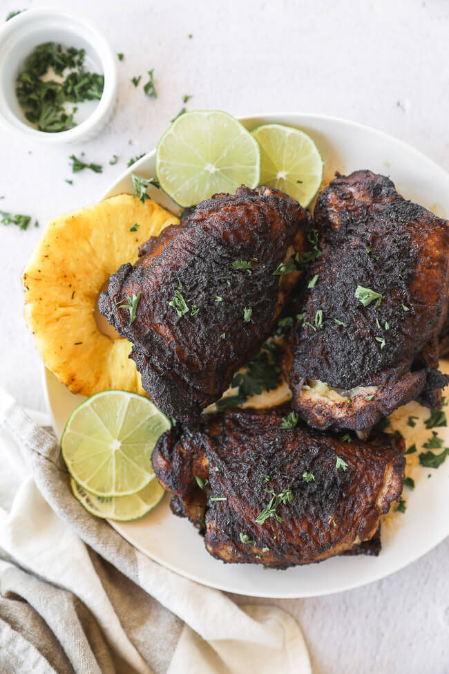 Easy slow cooker jerk chicken on a plate with pineapple and lime vertical image