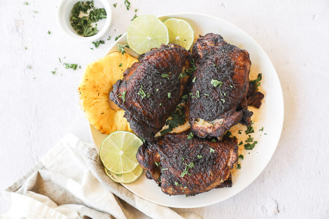 Easy slow cooker jerk chicken on a plate with pineapple and lime horizontal image