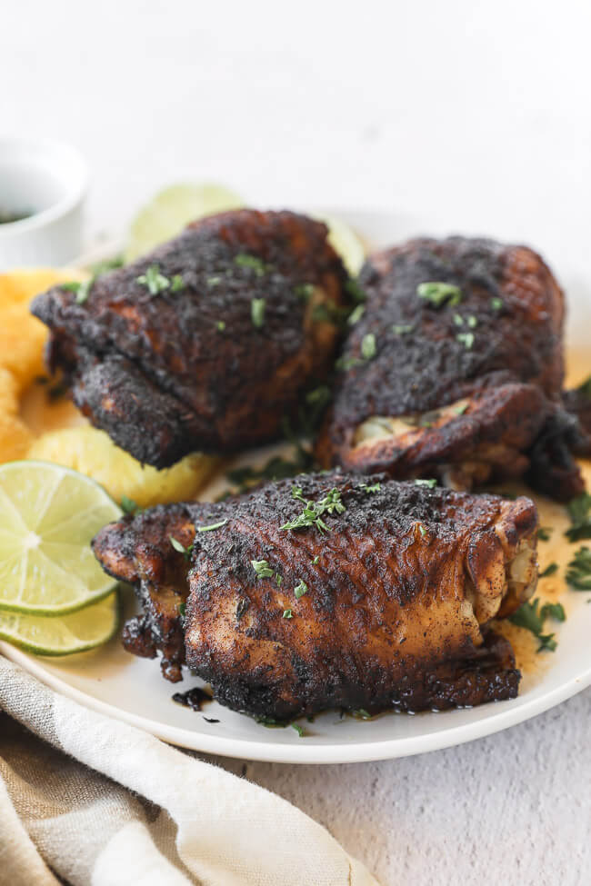 Easy slow cooker jerk chicken on a plate with pineapple and lime vertical angle image
