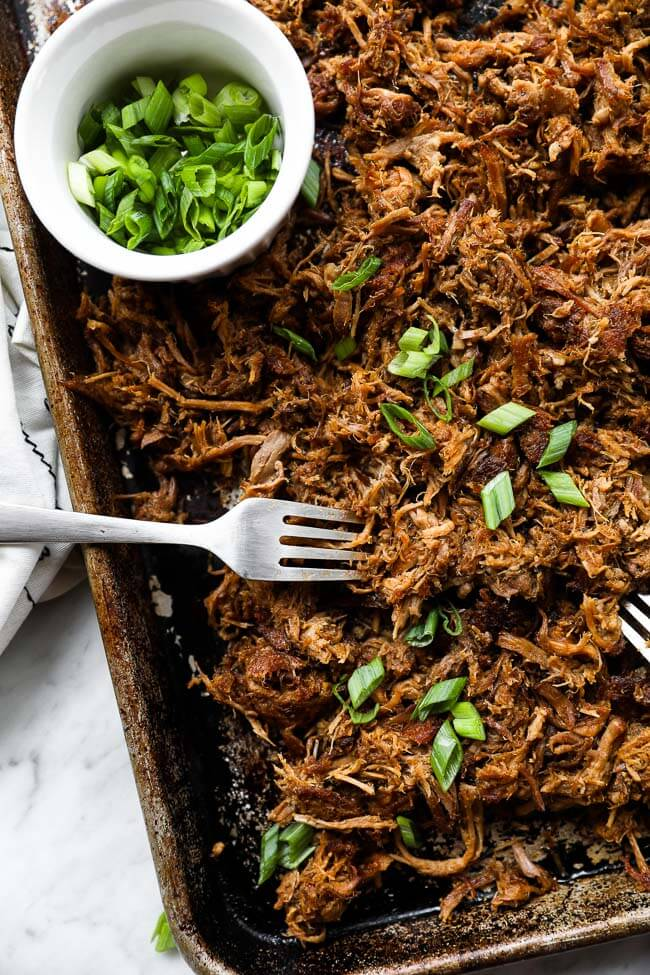 Easy slow cooker pulled pork on sheet pan with two forks and sliced green onions vertical image