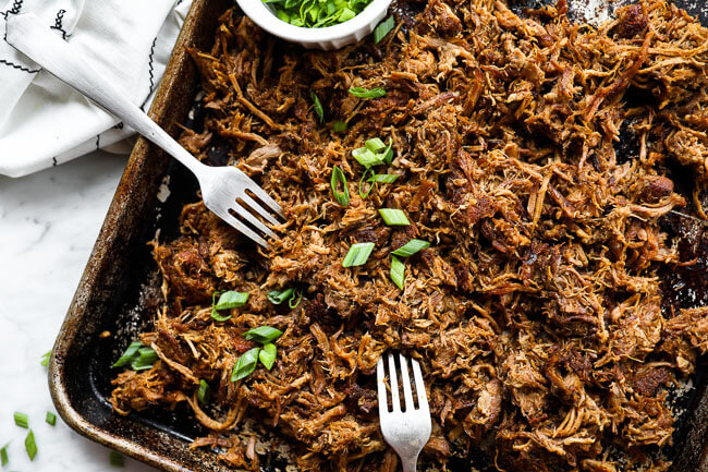 Easy slow cooker pulled pork on sheet pan with two forks horizontal image