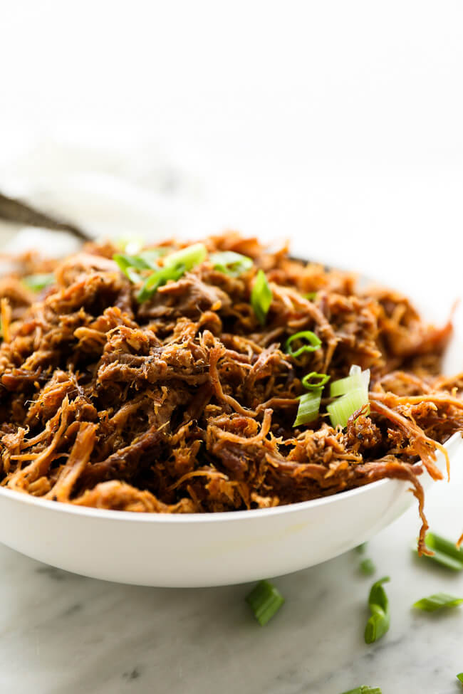 Easy slow cooker pulled pork in a bowl with sliced green onions on top vertical straight on image
