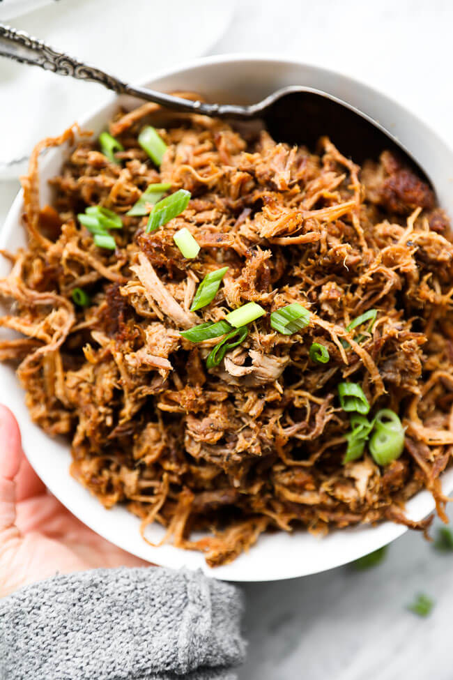 Easy slow cooker pulled pork in a bowl with sliced green onions on top and hand holding bowl vertical overhead image