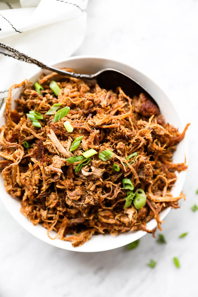 Easy slow cooker pulled pork in a bowl with sliced green onions on top vertical overhead image