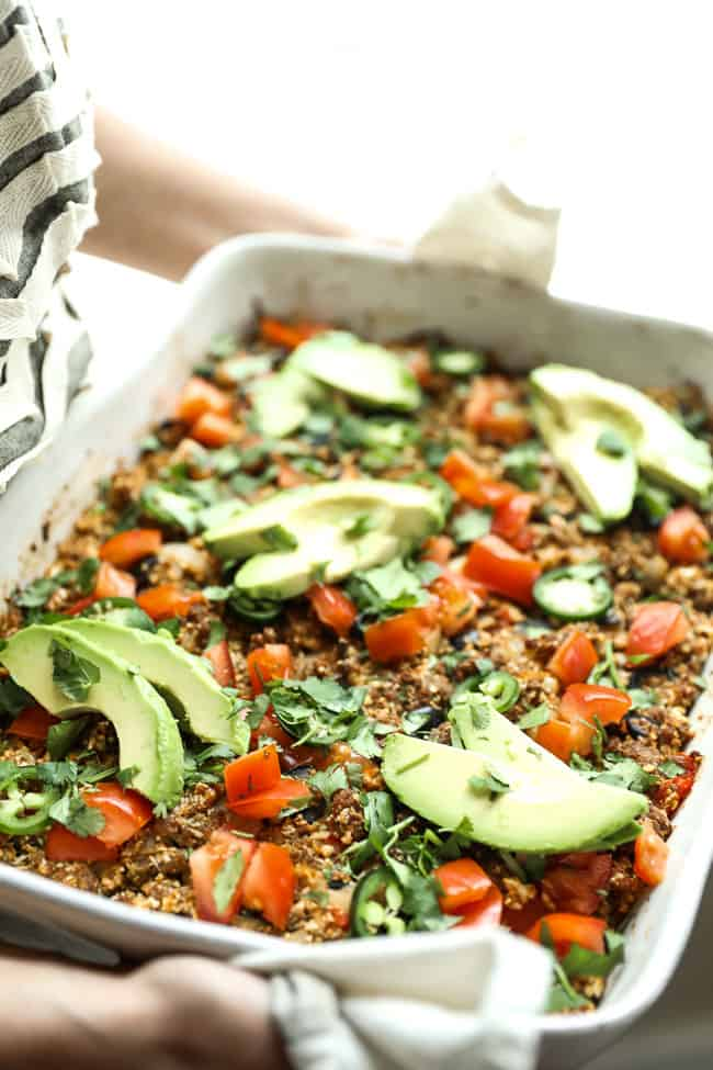 Image of holding easy taco casserole in white casserole dish, topped with chopped tomato, fresh cilantro, sliced jalapeño and avocado.