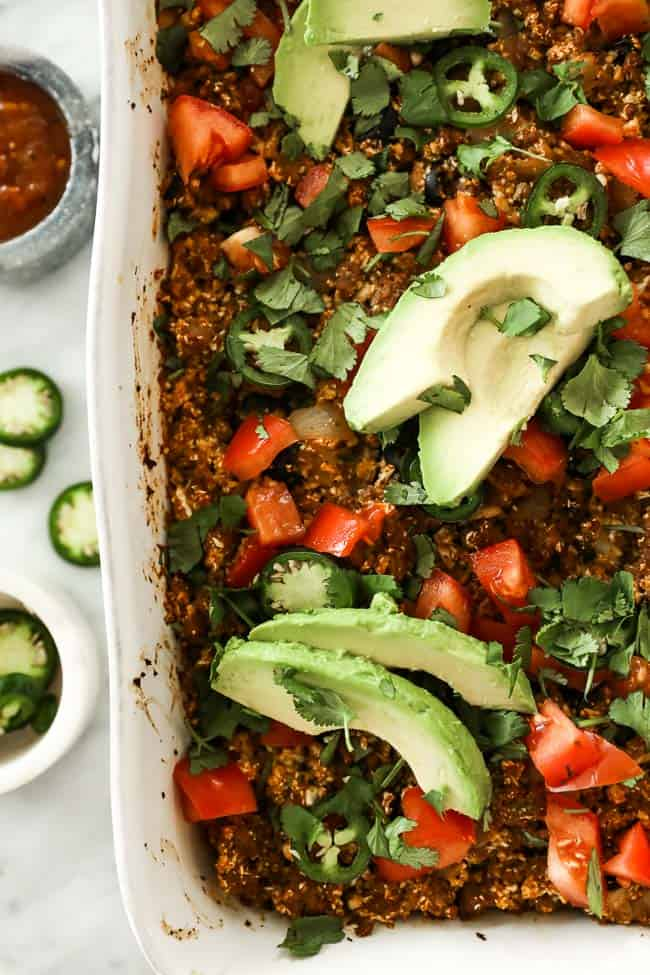 Image of easy taco casserole in white casserole dish, topped with chopped tomato, fresh cilantro, sliced jalapeño and avocado.