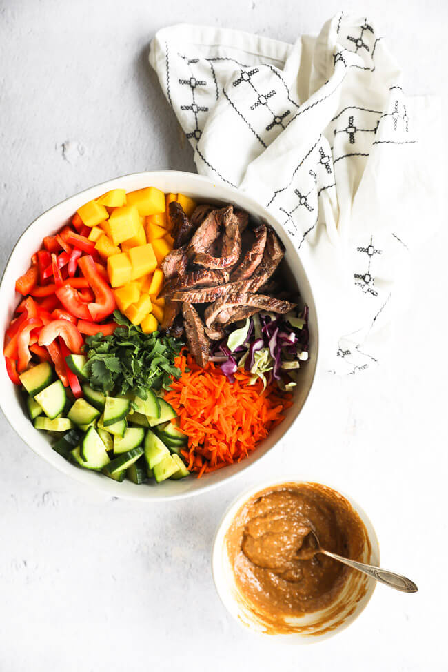 Thai beef salad in a large serving bowl made with cabbage, bell pepper, cucumber, cilantro, carrots, mango and skirt steak. Cashew sauce on the side.