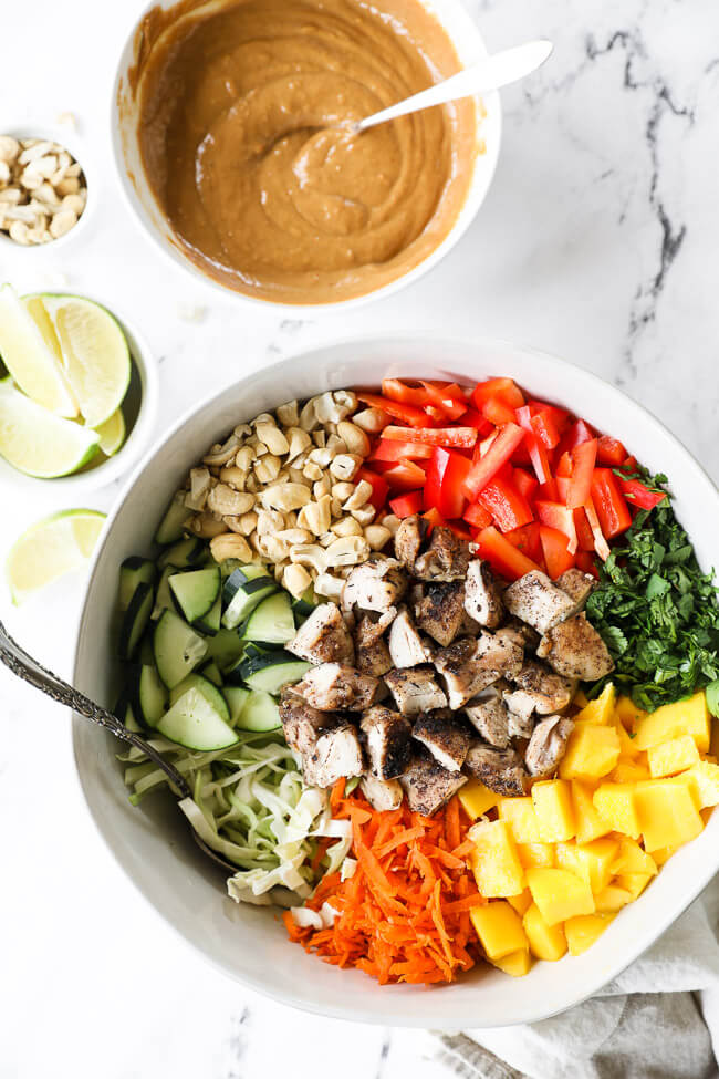 "Vertical overhead image of Thai chicken salad in a large serving bowl with all the ingredients separated out - cabbage, cucumber, cashews, red bell pepper, cilantro, mango, carrots, chicken and a ""peanut"" sauce and lime wedges on the side."