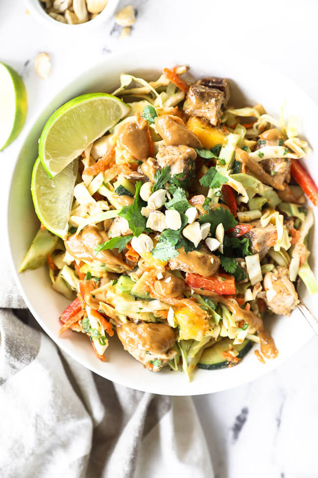 Vertical overhead image of Thai chicken salad all mixed up and served in a bowl with lime wedges, fresh cilantro and chopped cashews on top.