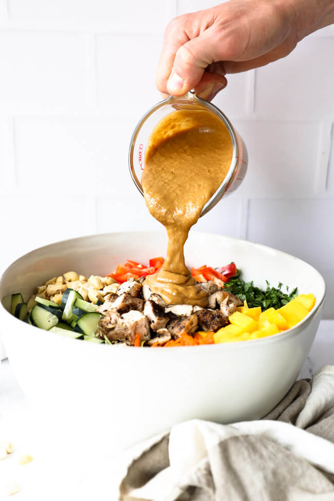 "Vertical straight on image of pouring the ""peanut"" sauce over the Thai chicken salad in a bowl."