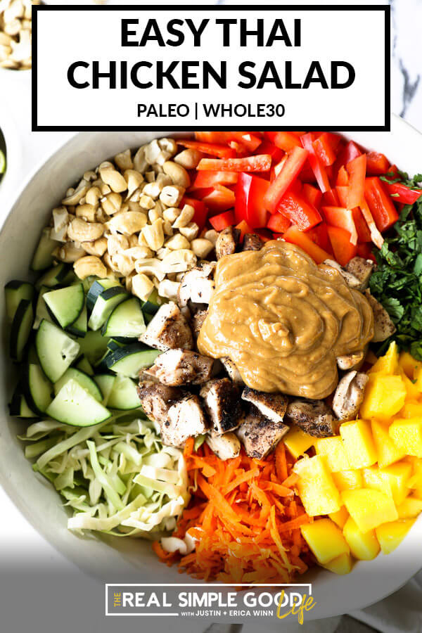 "Vertical overhead image of thai chicken salad in a large serving bowl with all the ingredients separated out - cabbage, cucumber, cashews, red bell pepper, cilantro, mango, carrots, chicken and a ""peanut"" sauce. Text overlay at top."