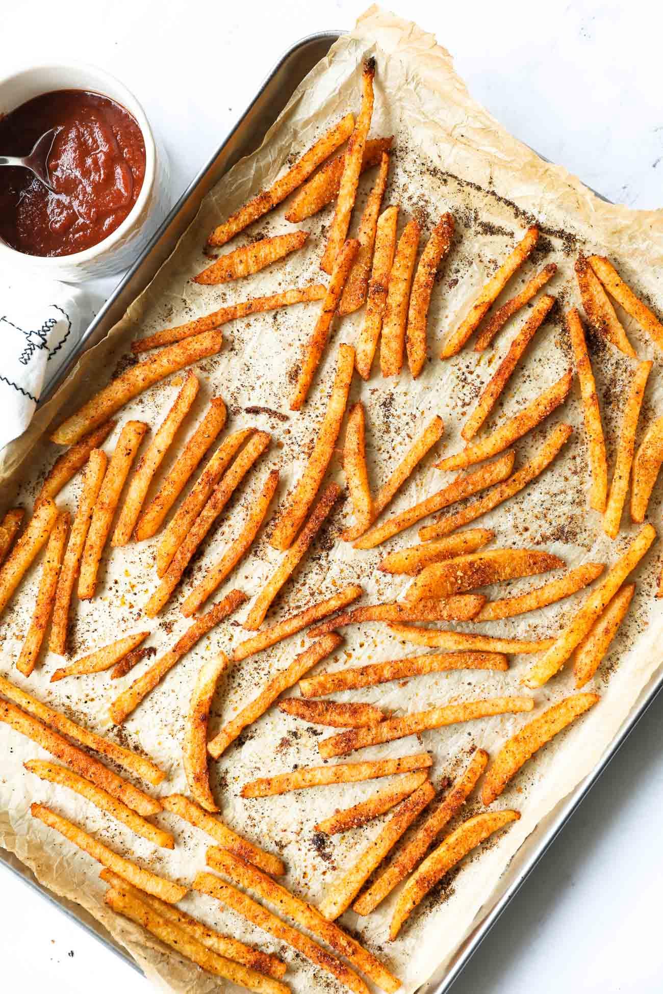 Seasoned crispy jicama fries on a sheet pan with ketchup on the side
