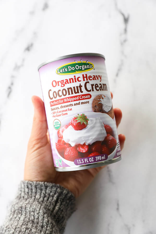Holding a can of our preferred coconut cream for making coconut whipped cream - Let's Do Organic Organic Heavy Coconut Cream.