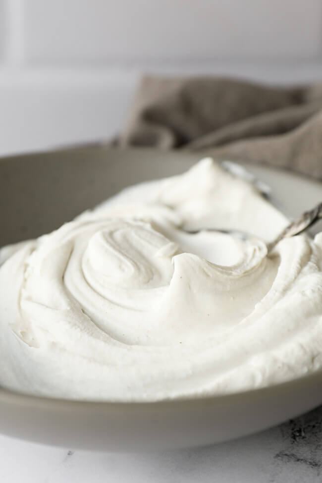 Close up angled image of coconut whipped cream in a bowl.