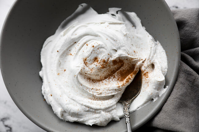 Vegan whipped coconut cream in a bowl with a serving spoon and sprinkled with cinnamon on top.