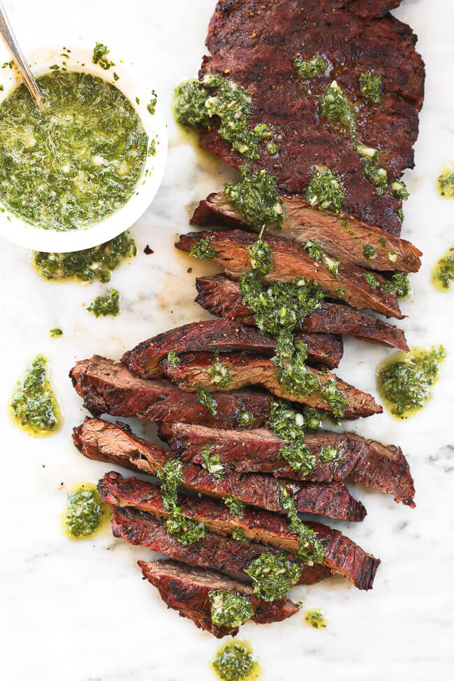 Skirt steak sliced on a marble board with fresh chimichurri sauce drizzled on top