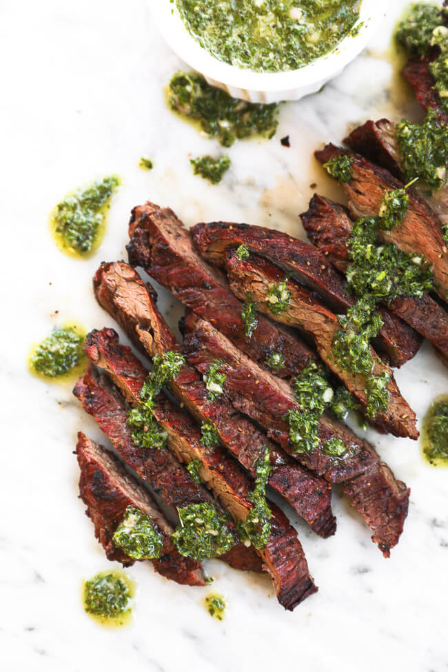 Sliced steak on marble with chimichurri sauce drizzled on top