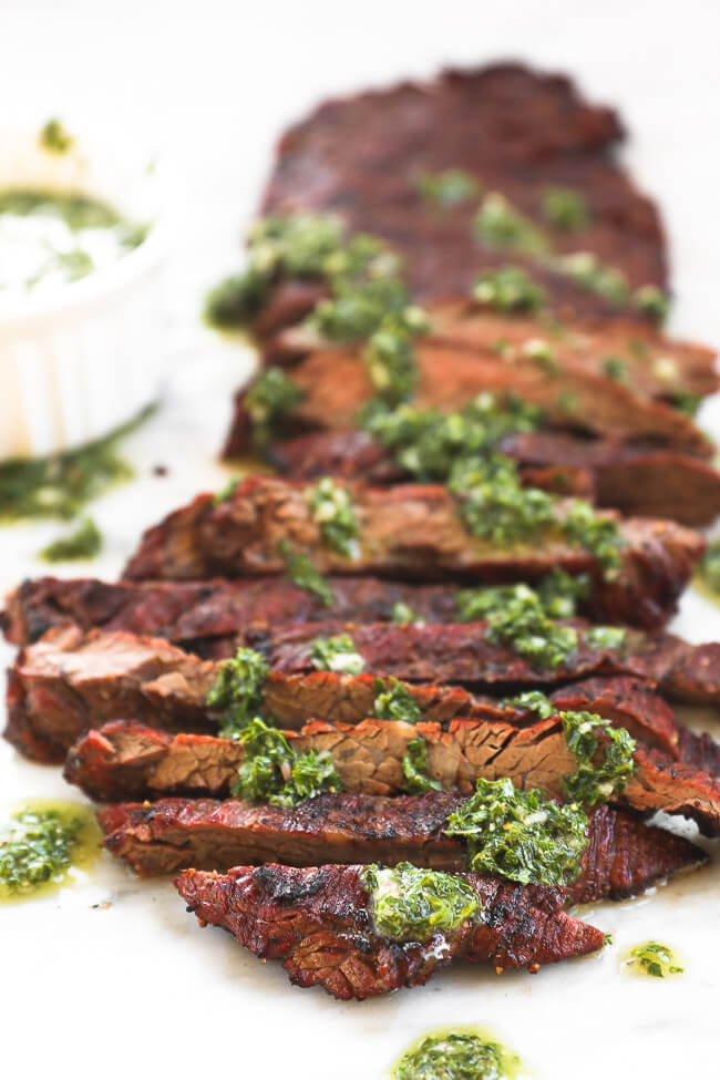 Close up image of sliced steak with chimichurri sauce drizzled all over