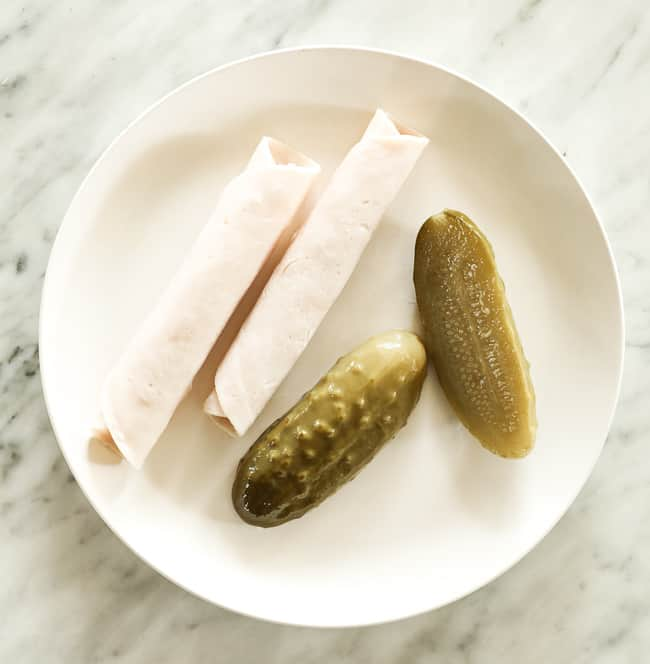 Pickles and rolled lunch meat on a plate