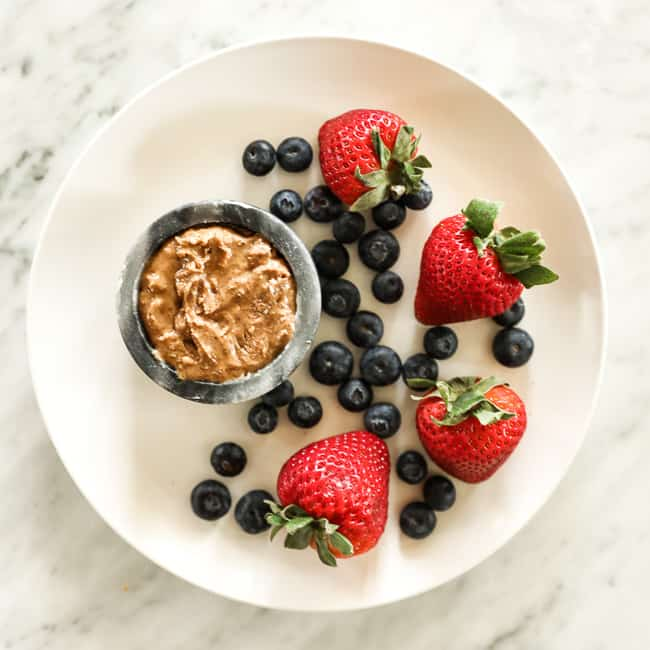 Strawberries and blueberries on a plate with almond butter