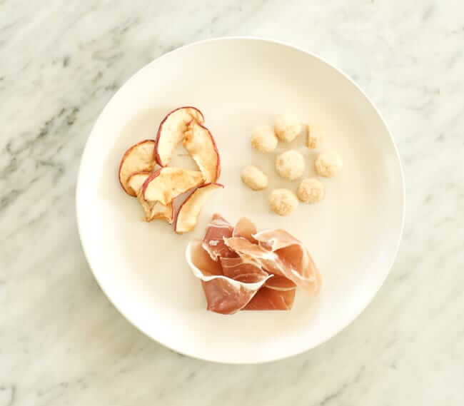 Dried apples, macadamia nuts and prosciutto on a plate
