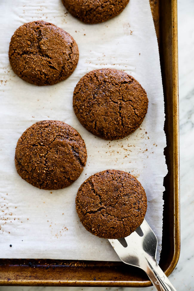 Overhead vertical image of ginger molasses cookies on a sheet pan with spatula lifting one cookie.